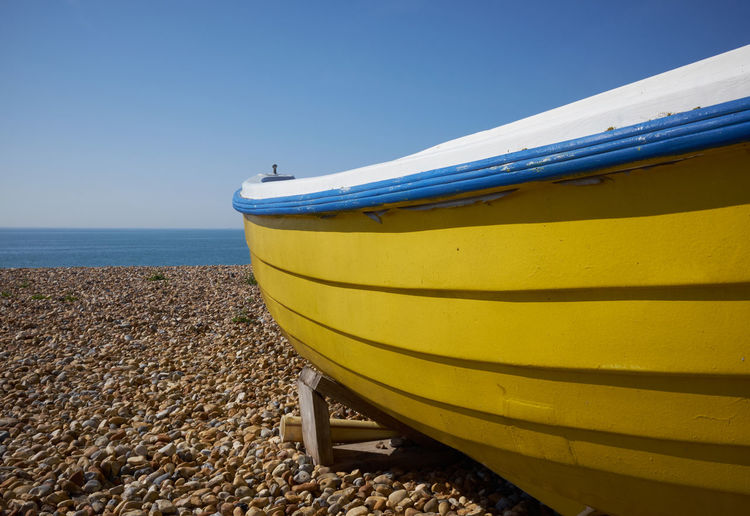 Yellow boat on beach against clear blue sky