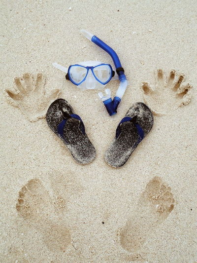 High angle view of snorkel with slippers and prints on sand