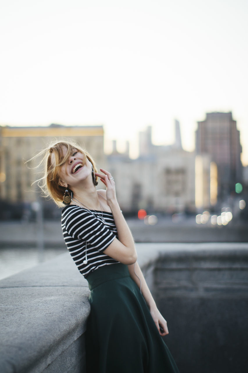Cheerful Woman Leaning Against Retaining Wall In City