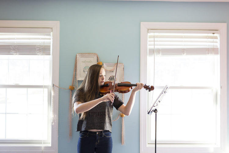 Woman playing violin while standing by window at home