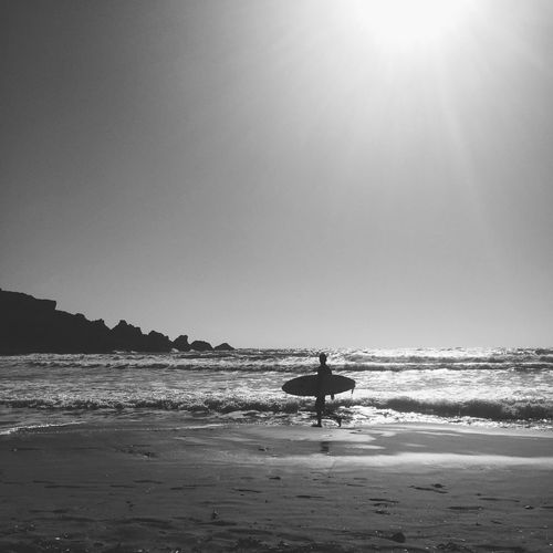 Surfer carrying surfboard on shore against clear sky