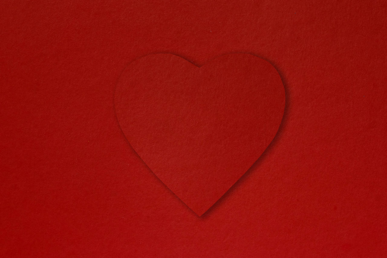 CLOSE-UP OF HEART SHAPE ON RED