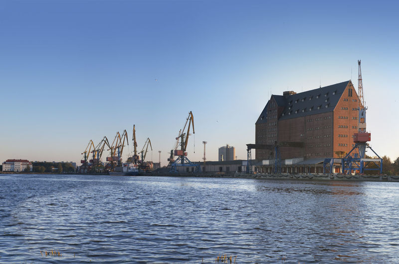 Cranes by river and buildings against clear sky