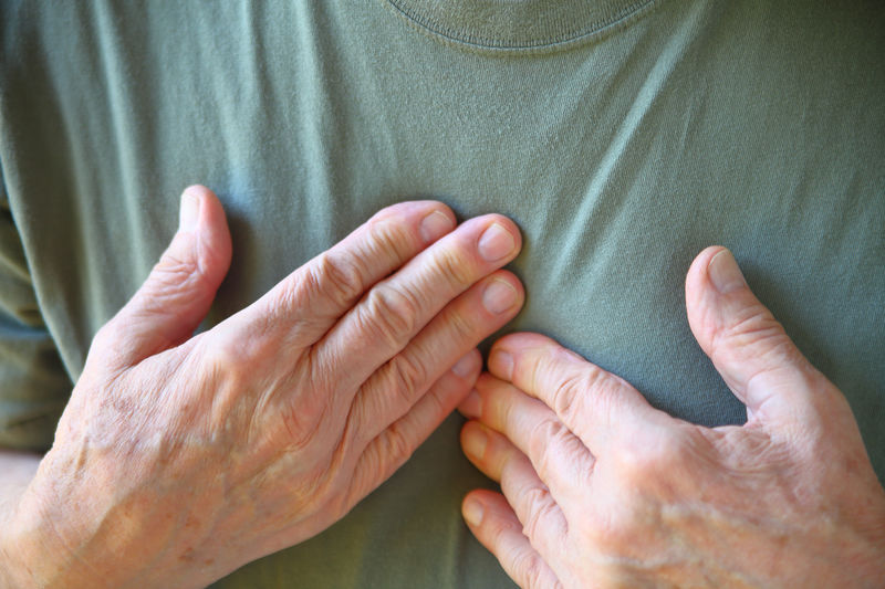 Midsection of man touching chest while suffering from pain