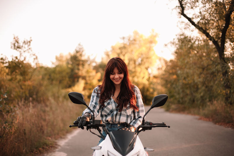 Portrait of young woman riding motorcycle on road
