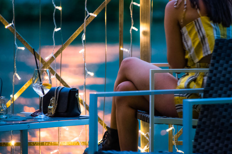 Young women sitting on chair with purse by illuminated string lights