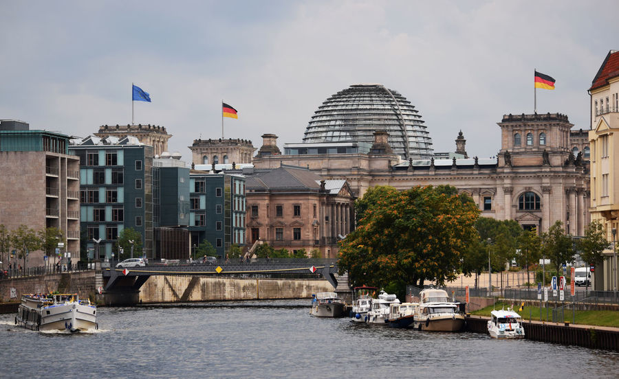 Angela Merkel Berlin Bundestag Deutschland European Union Power Spree Architecture Boat Boats Building Exterior Built Structure Eu European Union Currency Flag Germany Law National Icon Parliament Patriotism Politics And Government Reichstag River Water Waterfront Discover Berlin
