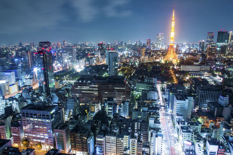 Illuminated tokyo tower amidst buildings in city