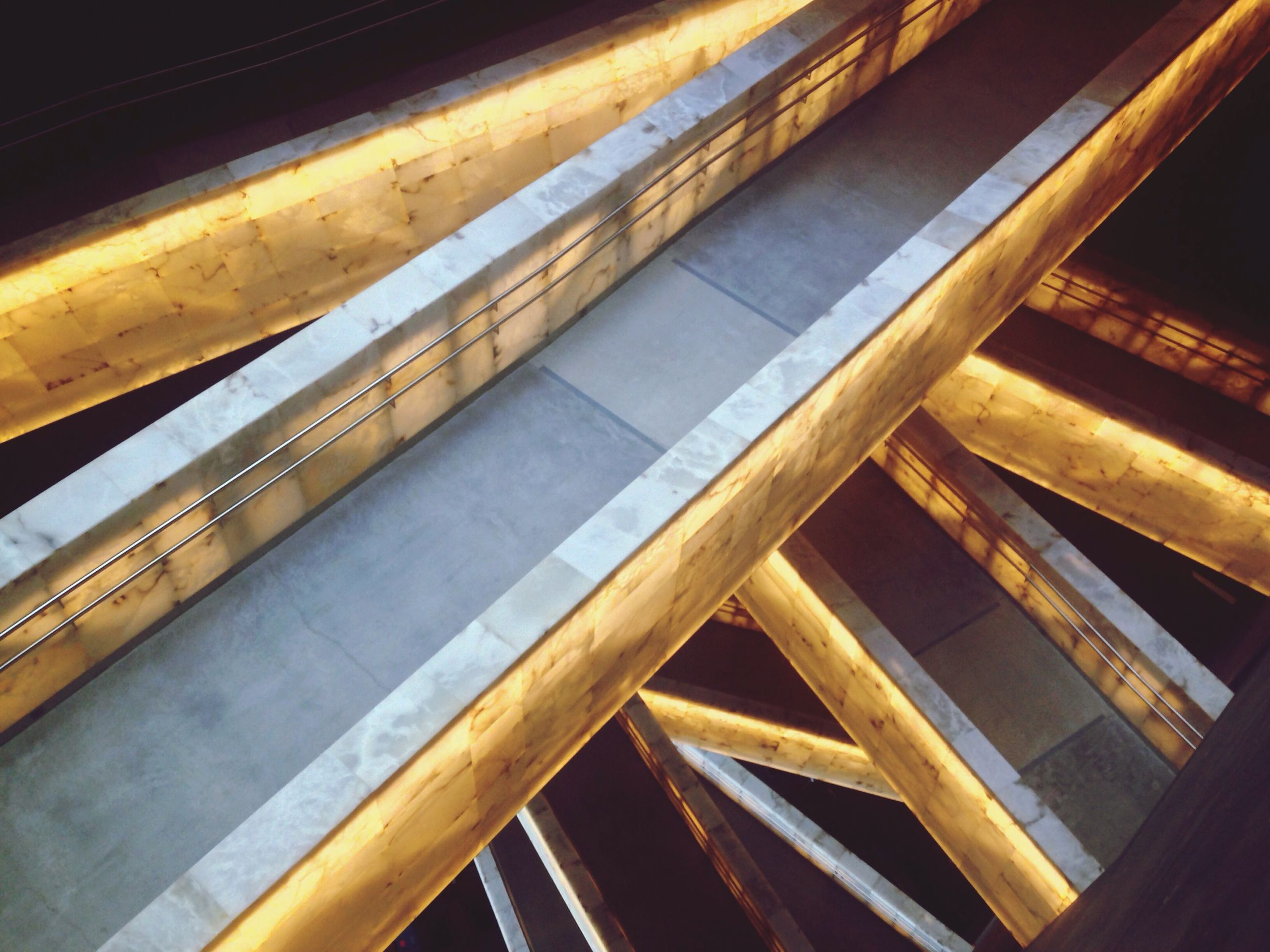 railing, steps, indoors, steps and staircases, staircase, low angle view, built structure, architecture, metal, pattern, night, spiral, high angle view, wood - material, ceiling, no people, spiral staircase, illuminated, escalator, close-up