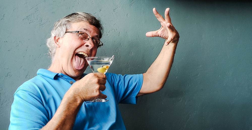 Man sticking out tongue while holding drink glass against wall