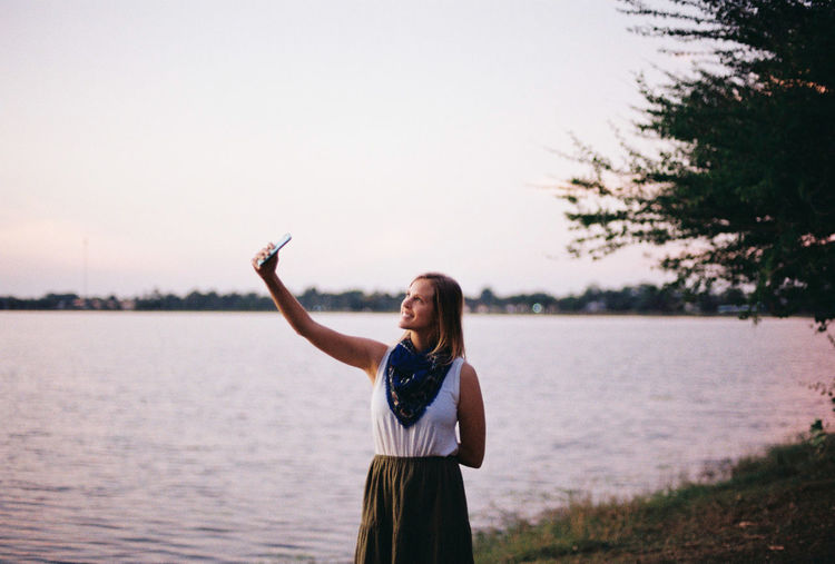 Woman Taking Selfie At Lakeshore Against Sky During Sunset