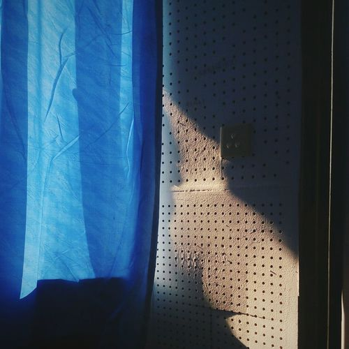 Sunlight falling on wall by blue curtain at home