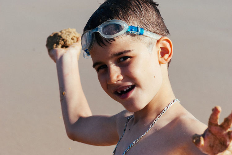 Close-up portrait of cute boy holding sand at beach