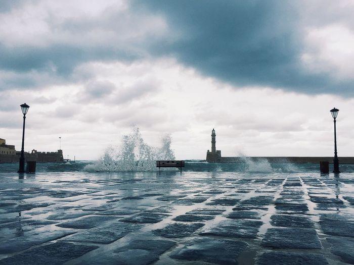 Waves splashing on promenade against cloudy sky