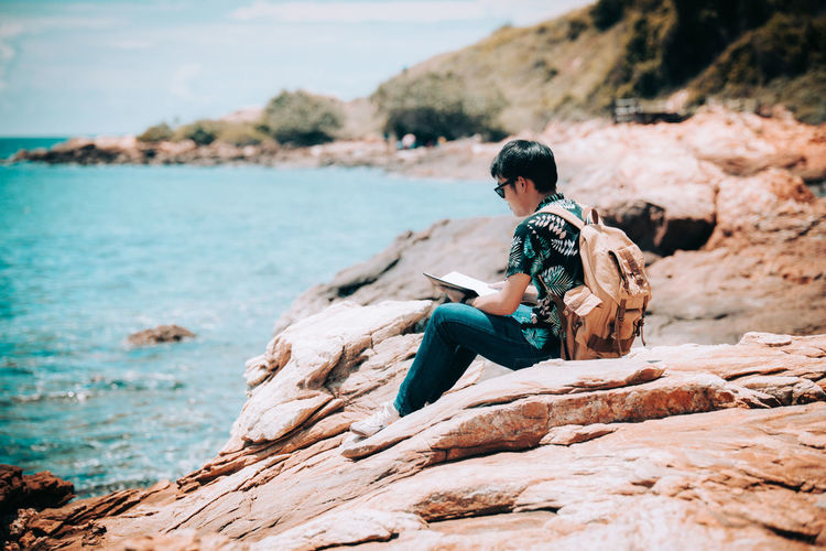 Side view of man reading book while sitting on rocky shore