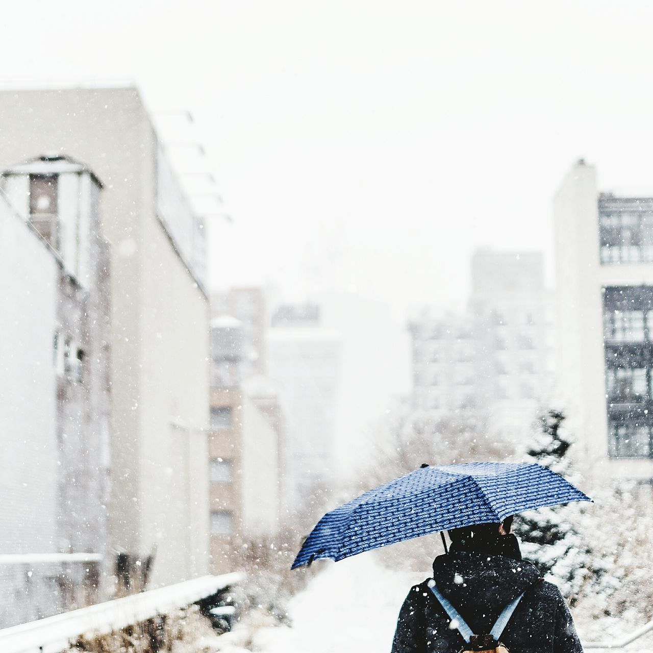 Rear View Of Man With Umbrella Walking On Snow Covered City Against Clear Sky