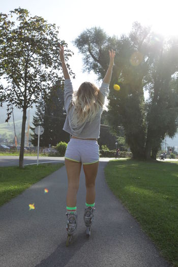 Woman rollerblading Rollercoaster Arms Raised Blond Hair Casual Clothing Clear Sky Day Full Length Grass Inline Skating Leisure Activity Lifestyles Nature One Person Outdoors Park - Man Made Space People Real People Rear View Roller Skate Roller Skating Skates Skating Tree Young Adult Young Women