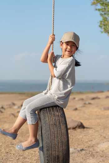 Portrait of girl sitting on tire at beach