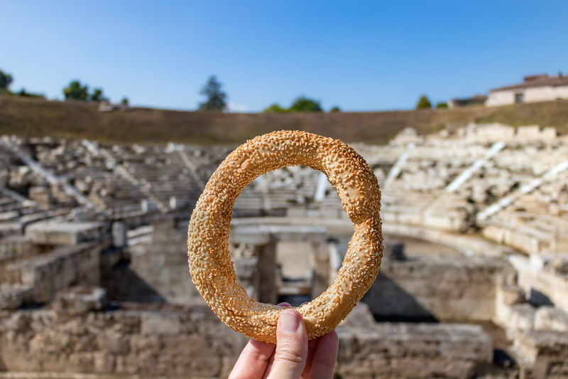 Midsection of person holding a greek koulouri snack against sky