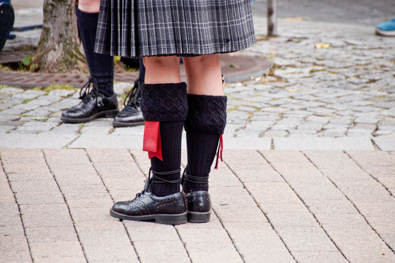 Low Section Of Girl And Boy Wearing Kilt While Standing On Street