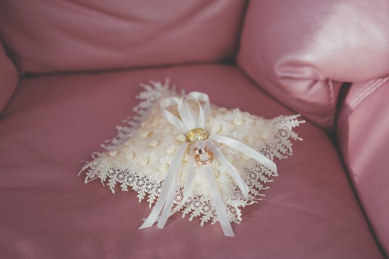 Close-Up Of Wedding Rings On Sofa