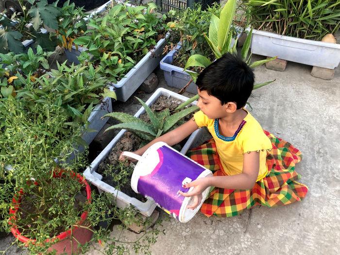 Full length of cute girl holding plants