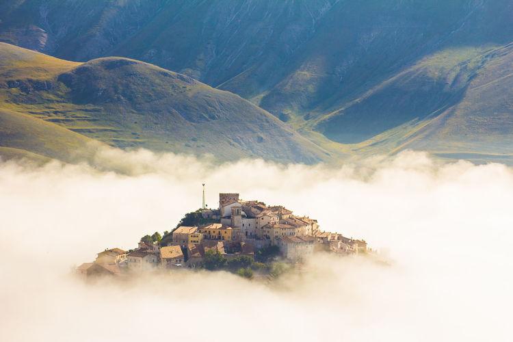 Buildings on mountain against sky