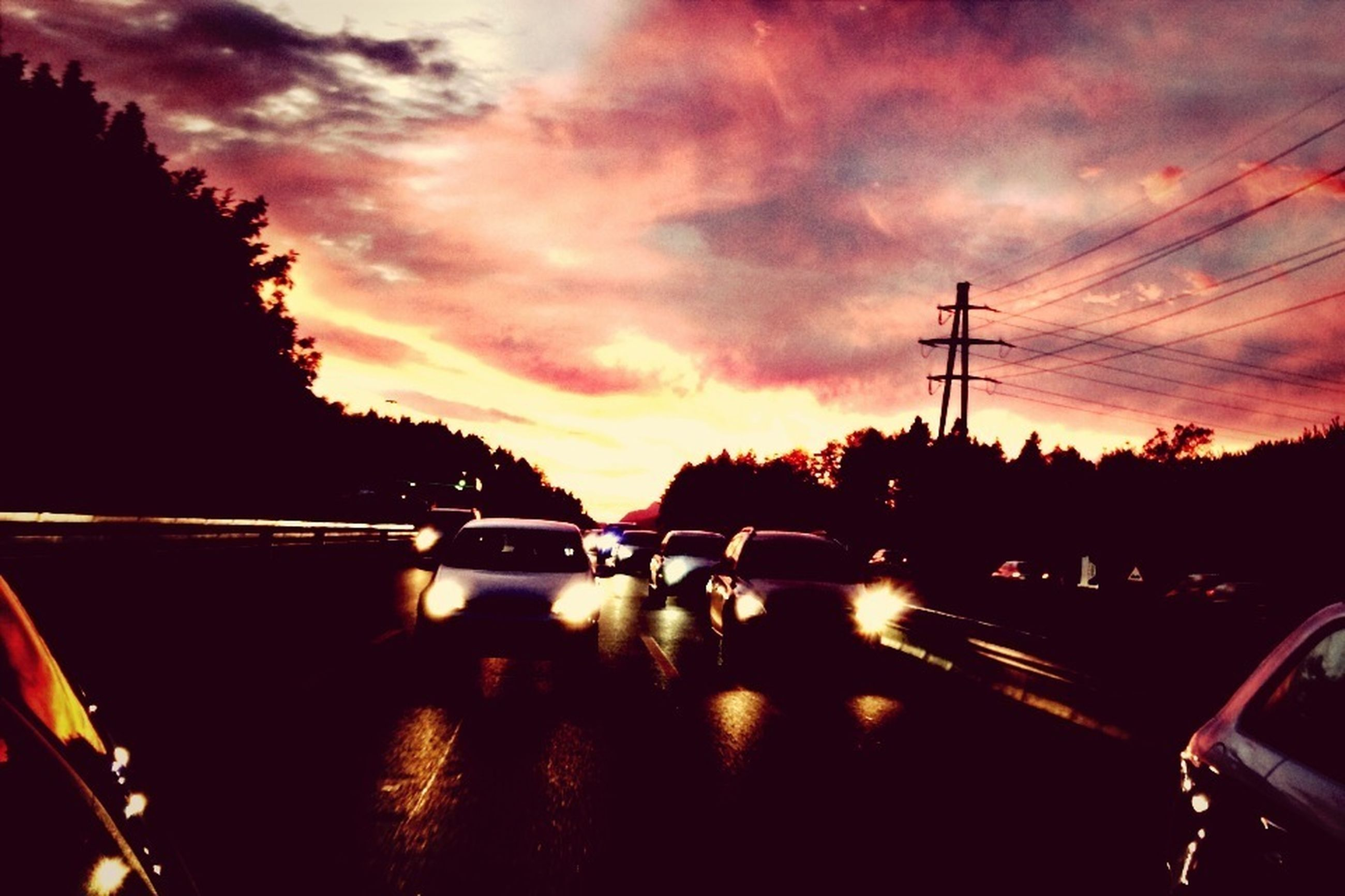 transportation, mode of transport, sunset, land vehicle, car, sky, silhouette, cloud - sky, orange color, on the move, travel, road, tree, electricity pylon, street, power line, vehicle interior, windshield, reflection, street light