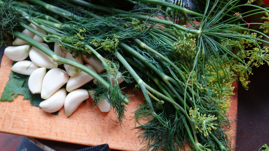 Close-Up Of Garlic And Dill On Cutting Board