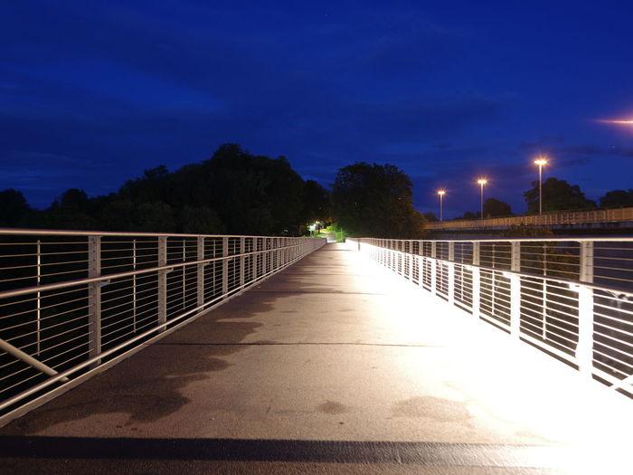 Illuminated footpath amidst trees against sky at night