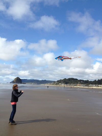 Low angle view of helicopter flying over beach against sky