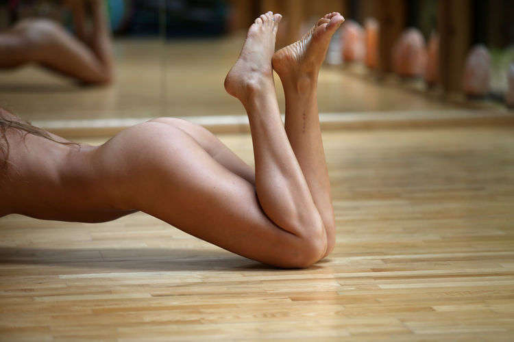 Low section of naked woman on floor