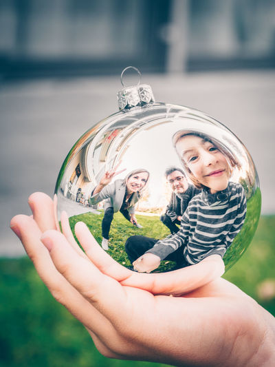 Christmas Decoration Christmas Mirror Family Child Childhood Holding Real People One Person Day Focus On Foreground Boys Human Body Part Women Girls Leisure Activity Hand Lifestyles Human Hand Outdoors Males  Men