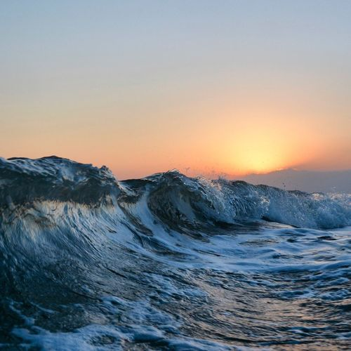 Waves curling in sea against clear sky during sunset