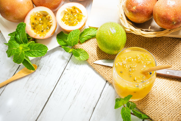 Food And Drink Food Healthy Eating Freshness Fruit Table Indoors  High Angle View Orange Leaves Leaf Yellow Drink Glass Passion Fruit Background Sweet Green View Juicy Color Refreshment Wellbeing Household Equipment Excrete Lose Weight