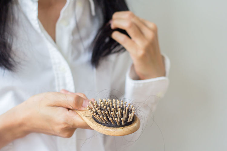 Midsection of woman holding hairbrush against wall