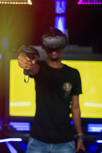 Young Adult Playing Games Virtual Reality Simulator Gamer Pointing Device Technology Communication Wireless Technology Fun One Person Front View Real People Standing Lifestyles Casual Clothing Leisure Activity Three Quarter Length Holding Night Yellow Waist Up Illuminated Indoors  Men Young Men Aiming