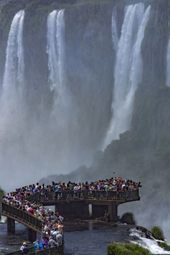 People on shore against waterfall