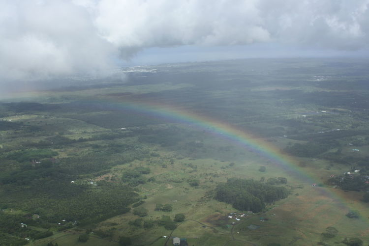 Scenic view of rainbow over land against sky