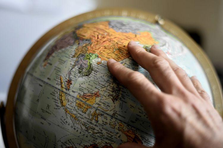 Cropped image of hand touching globe