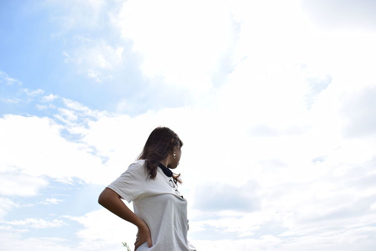 Low Angle View Of Woman Standing With Hand On Hip Against Cloudy Sky