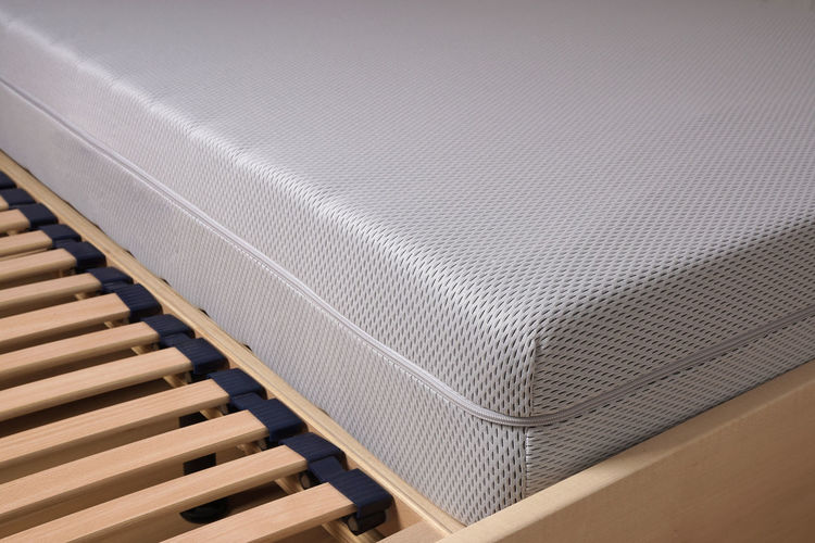 Close-up of cold foam mattress on wooden bed