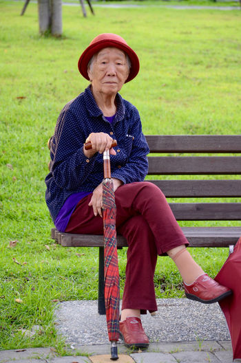 Portrait of senior woman with umbrella sitting on bench by grassy field at park