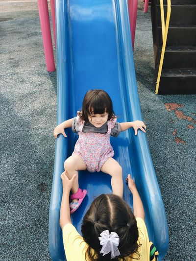 High angle view of siblings playing on slide at playground