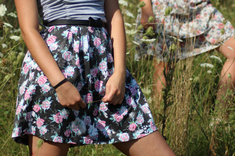 Midsection of woman wearing floral patterned skirt while standing on land