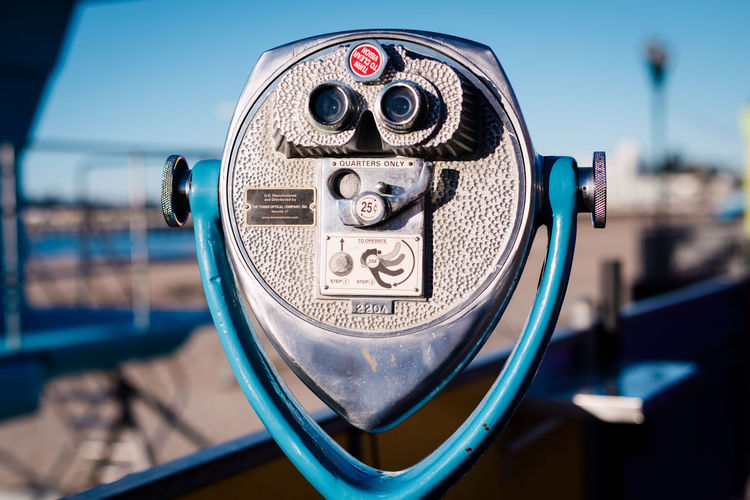 Close-up of coin-operated binoculars against clear blue sky