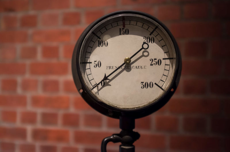 Close-up of pressure gauge against brick wall