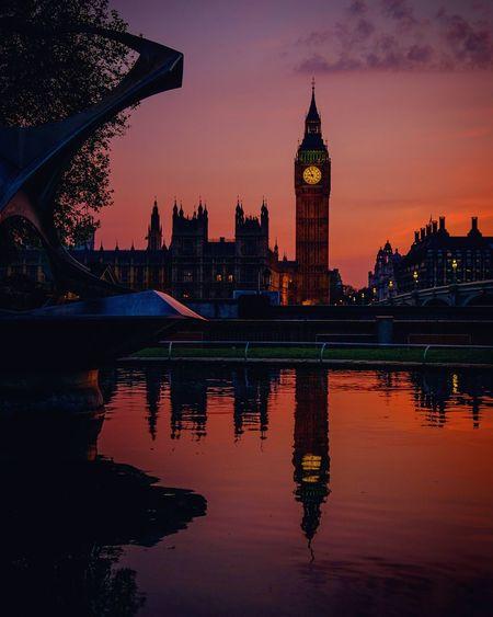 Reflection of big ben in river against orange sky at dusk