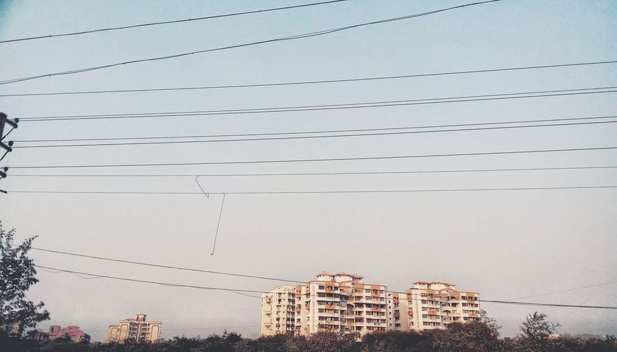 Low angle view of power lines against buildings in city