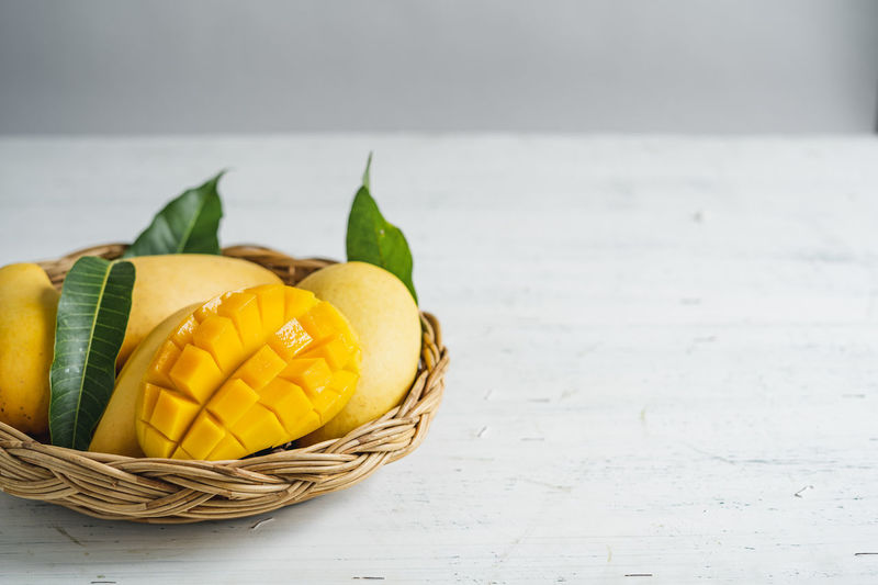 Mango in a basket Food And Drink Food Freshness Basket Healthy Eating Yellow Container Table Fruit Still Life Wellbeing No People Close-up Indoors  Focus On Foreground Citrus Fruit Wicker Selective Focus Vegetable Green Color Orange Vegetarian Food Temptation